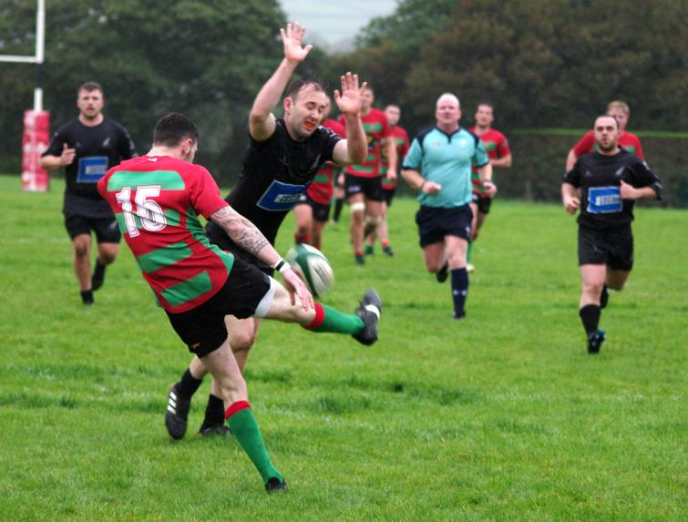 Neyland try scorer Patrick Bellerby charges down a kick