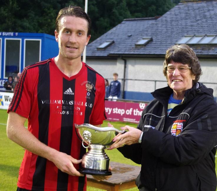 Goodwick United skipper Kieran O Brien receives Jubilee Cup off League chairperson Rowenna Lloyd