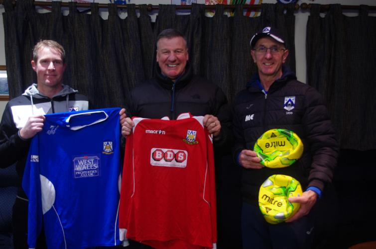 Bernie Armstrong (centre) receives football fit and balls from Haverfordwest County coaches Steve Batty (left) and Micky Ellis (right).