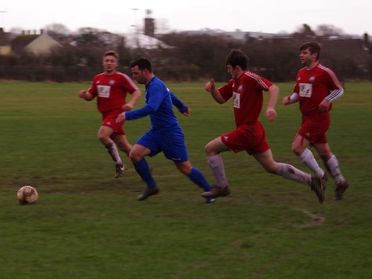 Merlins Bridge striker Steven McNabney takes on Milford United defenders
