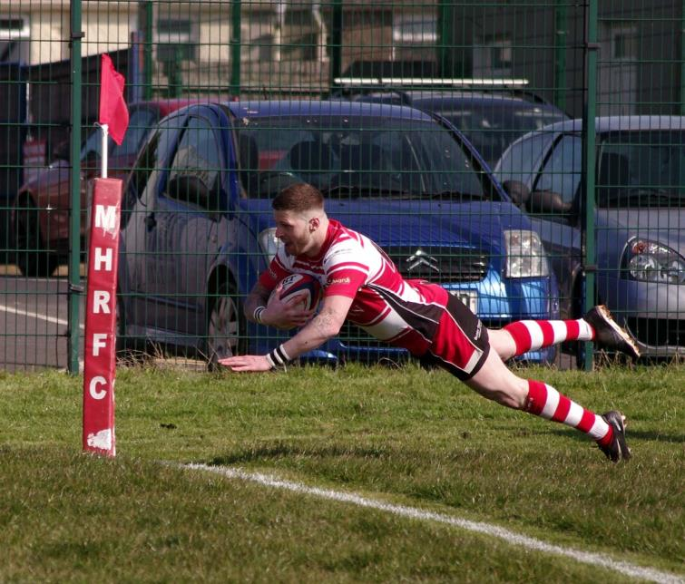 Milford Haven winger Jamie Lewis dives over for a try