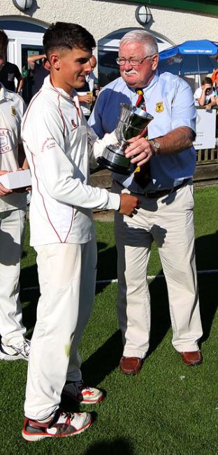 Iori Hicks receives the trophy from Gethin Evans