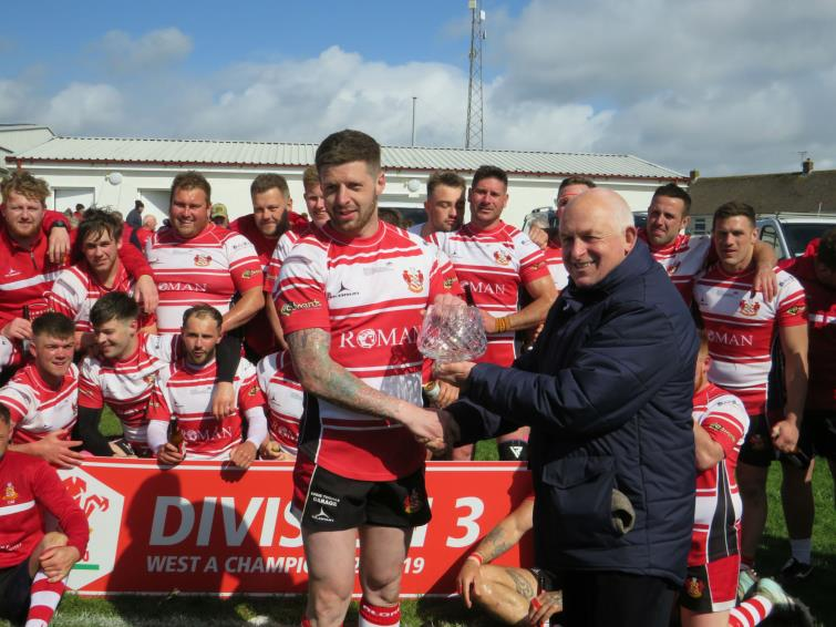 Mariners skipper Jamie Lewis recieves glassware from WRU representative Gordon Eynon